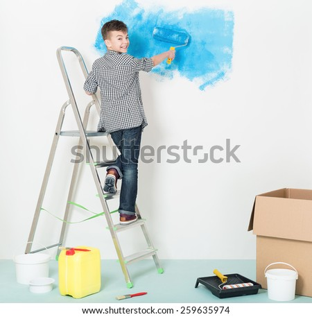 Happy boy makes repairs at home. Smiling boy with roller painting wall at room. - stock photo