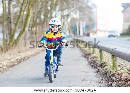 Happy boy of 5 years in safety helmet and colorful raincoat riding his first bike and having fun on cold  day, outdoors. Active leisure with children in winter, spring or autumn. - stock photo