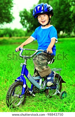 Happy boy on a bicycle in a summer park.