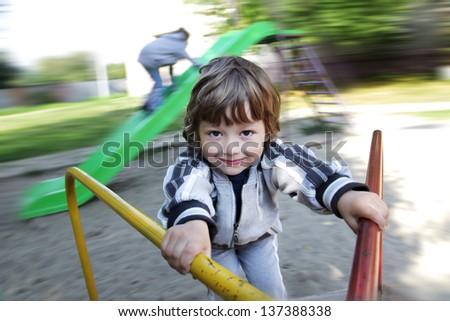 happy boy on carousel outdoors - stock photo