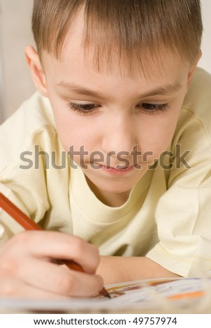 happy boy on the carpet and drawing a picture