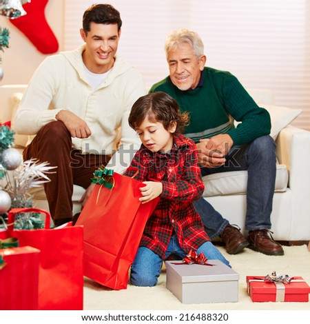 Happy boy opening gifts at christmas and father and grandfather watching - stock photo