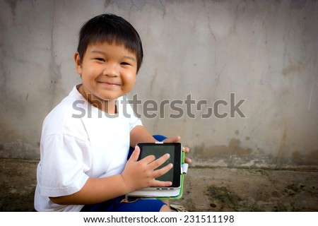 Happy boy outdoors using his tablet computer for educating and playing  - stock photo