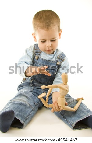 Happy boy playing and showing his wooden figurine