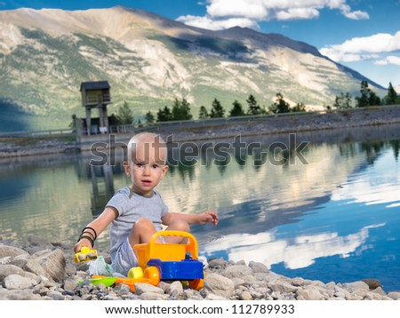 Happy boy playing at the lake in Canmore, Banff, Alberta. Hair loss due to strong Chemo therapy regimen.