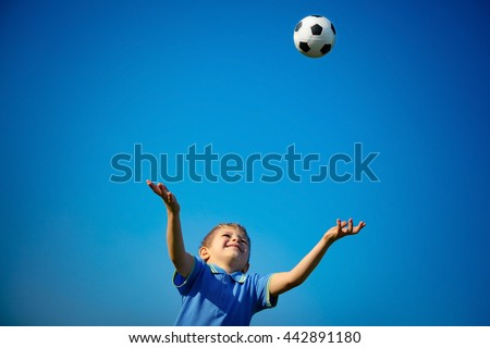 Happy boy playing ball, cute little child catching ball over blue sky background, playing football in sunny summer day, happy healthy childhood - stock photo