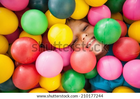 Happy boy playing in ball pool at a party - stock photo