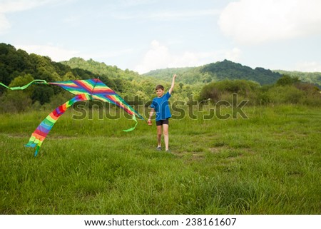 Happy boy playing in field with multicolor kite