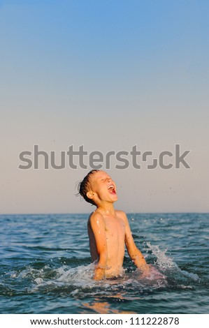 Happy boy playing in sea - stock photo