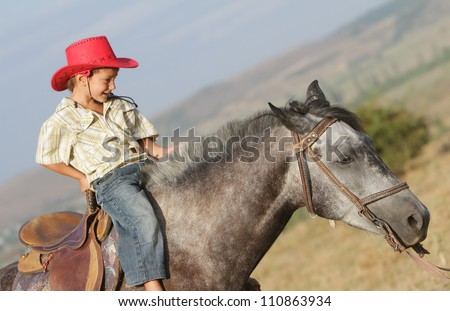 happy boy riding horse on natural background - stock photo