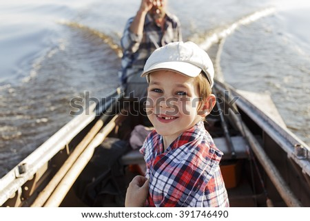 happy boy riding in a boat with his grandfather. child cheerfully smiling a toothless smile while sitting in a motorboat. the concept of connection between generations. return from fishing - stock photo