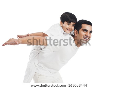 Happy boy riding piggyback on his father - stock photo