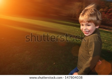 Happy boy running in park at sunset - stock photo