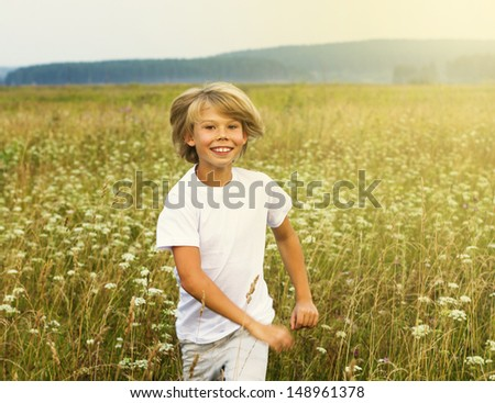 Happy boy running on summer field - stock photo
