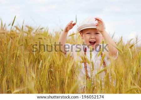 happy boy running on wheat field - stock photo