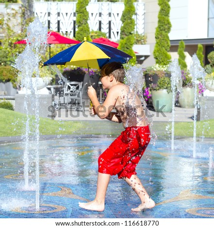 Happy boy running through water in fountain with umbrella. - stock photo
