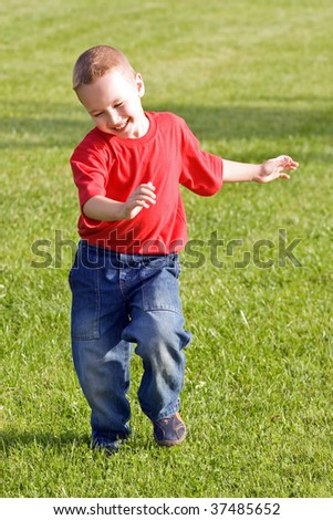 Happy boy runs on a green grass
