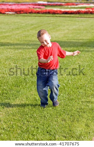 Happy boy runs on a green grass - stock photo