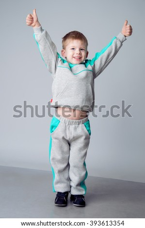 Happy boy showing sign okay with fingers. He with blond hair and dressed in a grey sports suit. Sporting style. Studio shot - stock photo