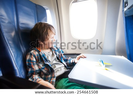 Happy boy sit in plane with toy model on table - stock photo