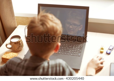 Happy boy sitting at his desk With laptop computer