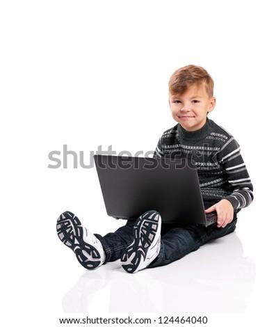 Happy boy sitting on floor with laptop on white background - stock photo