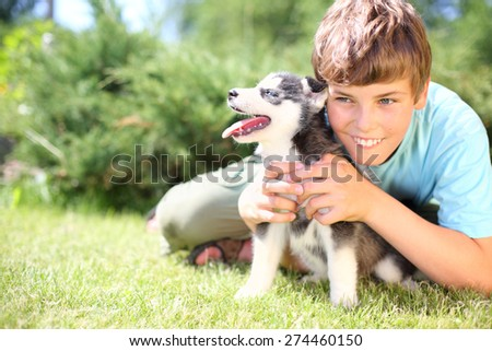 Happy boy sitting on the grass with puppy husky - stock photo