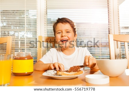 Happy boy spreading chocolate with knife on toast
