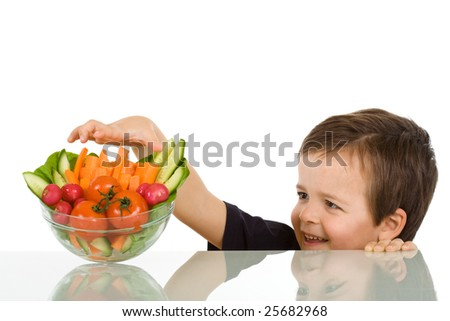 Happy boy stealing from the vegetables bowl - isolated