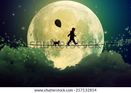 Happy boy teenager and cat walking with balloon on a tight rope above clouds with moonlight moon background. Happiness care free concept. Elements of this image furnished by NASA - stock photo