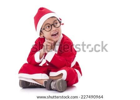 Happy boy wearing Santa Claus uniform. - stock photo