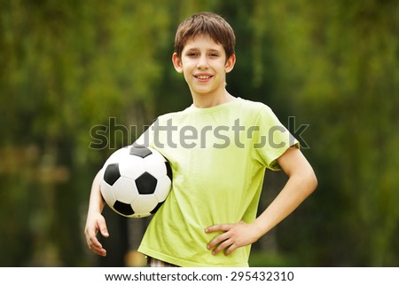 Happy boy with a soccer ball in hand - stock photo