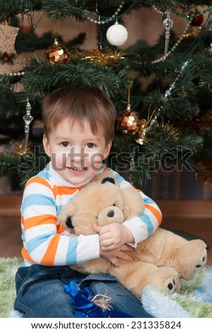 Happy boy with a teddy bear in a Christmas tree (3 years old) - stock photo