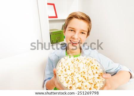 Happy boy with big popcorn bowl on white sofa - stock photo