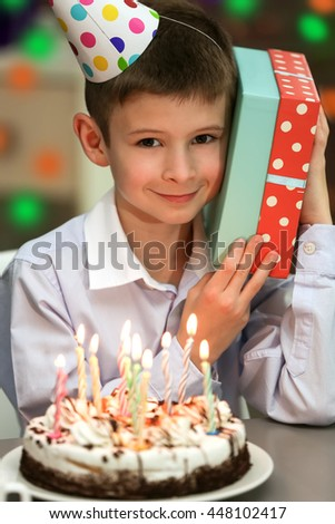 Happy boy with birthday cake and gift box