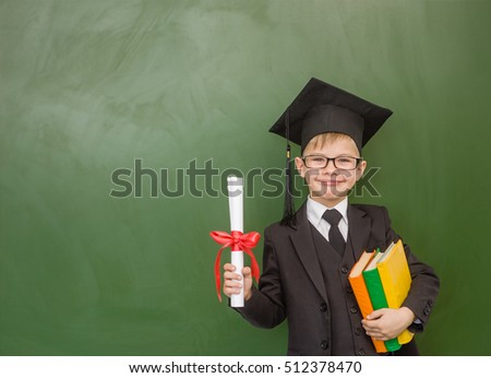 Happy boy with books and a diploma in graduation cap stands near a school board
