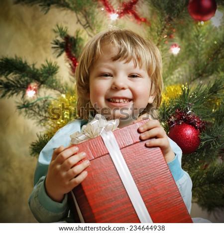 happy boy with christmas gift near Christmas tree - stock photo