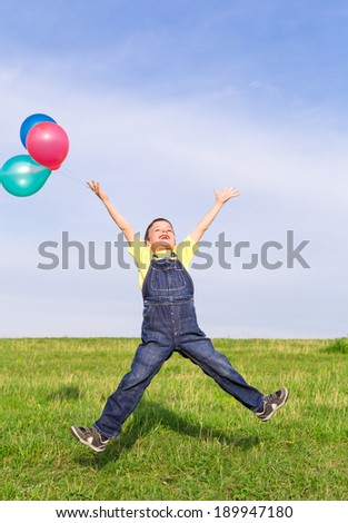 Happy boy with colorful balloons jumping on green field, outdoors - stock photo