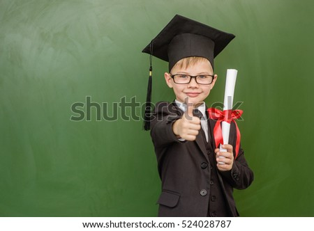 Happy boy with diploma in graduation cap stands near a school board and showing thumbs up