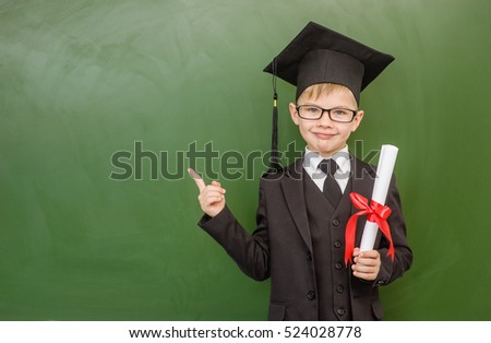 Happy boy with diploma in graduation hat points on empty green chalkboard