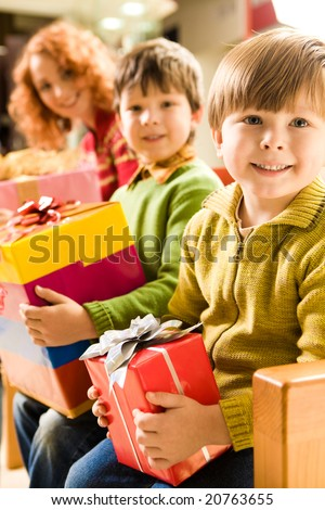 Happy boy with gift in hands sitting in supermarket on background of his brother and mother