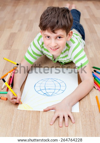 Happy boy with globe earth world icon and crayons lies on floor - stock photo