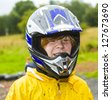 happy boy with helmet at the kart trail in rain with dirty face and clothing - stock photo