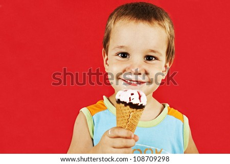 Happy boy with ice cream cone. Isolated on red background. - stock photo