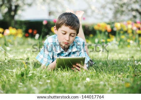 Happy boy with laptop outdoors in spring park - stock photo