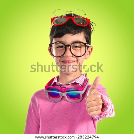 Happy boy with many glasses over colorful background