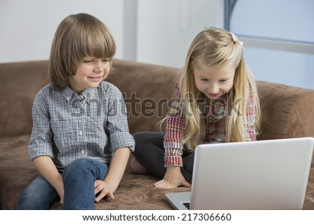 Happy boy with sister using laptop on sofa - stock photo