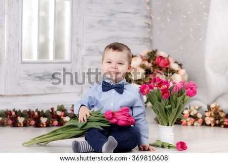 Happy boy with tulips. March 8 - stock photo