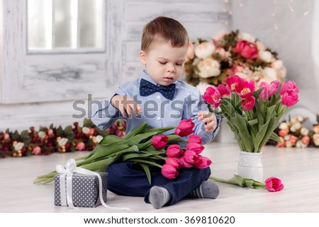 Happy boy with tulips. March 8, International Women's Day, Mother's Day - stock photo