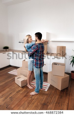 Happy boyfriend and girlfriend hugging in kitchen with boxes and holding keys from apartment.Copy space